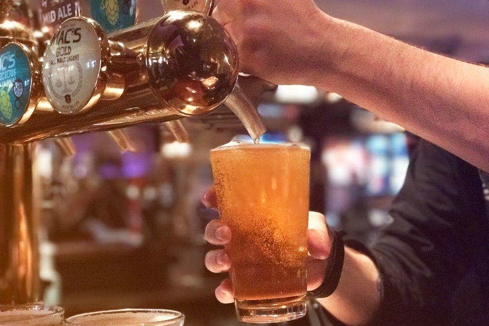 pub, com torneiras de cervejas e uma pessoa se servindo