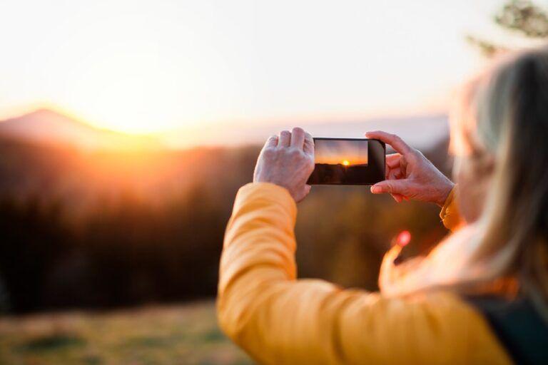 Mulher fotografando o nascer do sol
