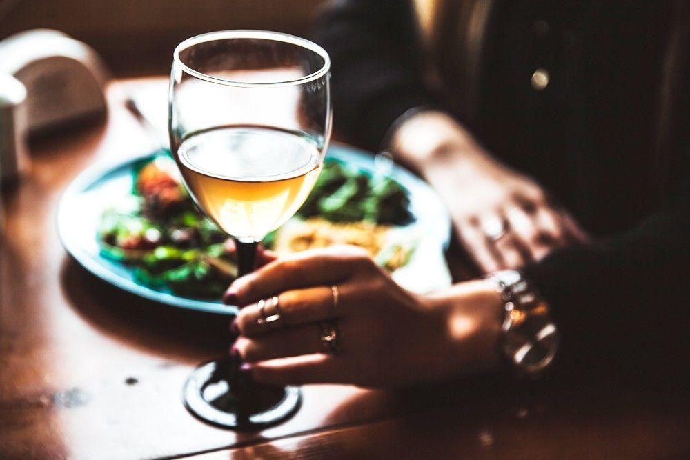 Mulher tomando vinho e almoçando