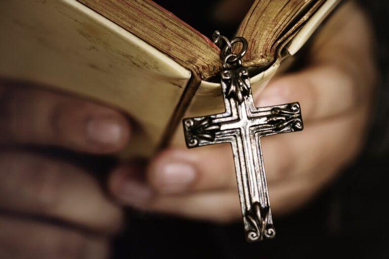 Mão com Bíblia e rosário com cruz.