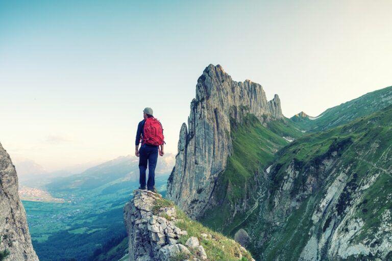 Homem no alto de uma montanha de pedra.